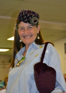 Dianne Tobias models her pillbox hat with flower, and a pretty braided purse