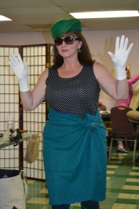 Deb Lynch channels Jackie O in her pillbox hat, sunglasses, and gloves