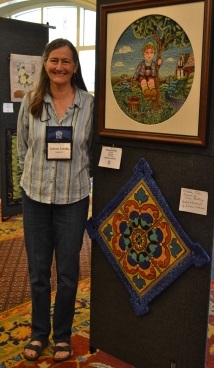 "Dianne Tobias poses next to her ""tile"" rug (lower one displayed) with a braided frame"